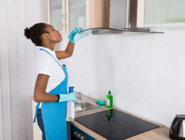56277035-young-african-woman-cleaning-cooker-hood-with-rag-in-kitchen
